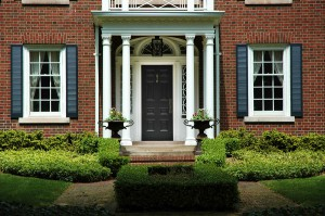 Red brick house with black shutters and green shrubs with front door flanked by pillars and two flower iron urns; luxury home / house